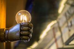 Tenir une ampoule dans une main image stock