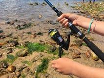 Tenir une canne à pêche et une ligne Images stock