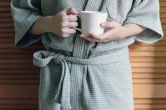 Tenir une tasse dans le peignoir Photographie stock