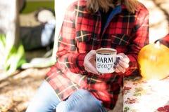 Tenir une tasse de chocolat chaud au terrain de camping dans la chute photos libres de droits