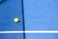 Tenis court. Yellow tennis ball on blue track and shadow network Stock Photo