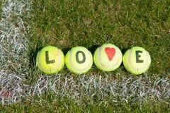 Tenis del amor - pelotas de tenis con el corazón y las letras Foto de archivo