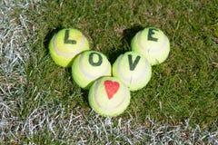 Tenis del amor - pelotas de tenis con el corazón y las letras Imagenes de archivo