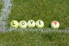 Tenis del amor - pelotas de tenis con el corazón y las letras Fotografía de archivo libre de regalías