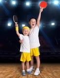 Tenis del juego de dos hermanos en el pasillo de deportes campeones fotos de archivo libres de regalías