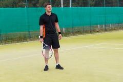 Tenis del juego del hombre joven al aire libre en campo de tenis en la madrugada Imagen de archivo