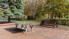 Bench and a tennis table with fallen yellow foliage from the trees, in the autumn in the park a warm day. Tenis table and a bench with fallen leaves on them in Stock Images