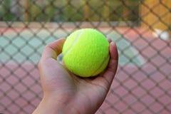 Tenisowa piłka na ręki plamy tła sądzie obraz royalty free
