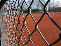 Tenisowy sąd w żwirze przeglądać ochronną drucianą siatką Fotografia Stock