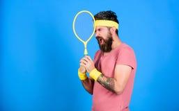 Tenisowy sport i rozrywka Atleta chwyta tenisowy kant w ręce na błękitnym tle Tenisowego klubu pojęcie Mężczyzna brodaty zdjęcia royalty free