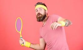 Tenisowy sport i rozrywka Atleta modnisia chwyta tenisowy kant w ręki czerwieni tle Mężczyzna modnisia brodata odzież obrazy stock