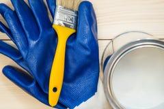 Tenn- can av hushållmålarfärg, en borste och par av handskar fotografering för bildbyråer