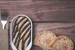 Tenn- can av små stackare, sardiner med brödstycken och gaffeln på trätabellen Bästa sikt och fritt utrymme royaltyfri fotografi