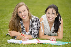Outdoor study. Tennage students lying on the grass and study together Stock Image