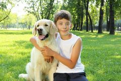 Tennager boy in the park with a dog. Teenager boy in the park with a golden retriever dog Royalty Free Stock Photography