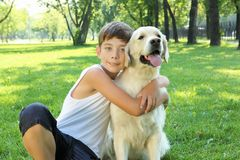Tennager boy in the park with a dog. Teenager boy in the park with a golden retriever dog Stock Photo
