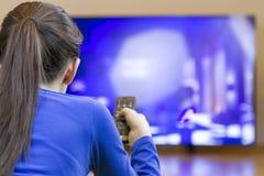 Tennager dziewczyna kłaść w dół i ogląda przy tv Obrazy Royalty Free