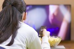 Tennager dziewczyna ogląda tv z pilot do tv Fotografia Royalty Free