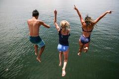 Tennagers que salta en el lago Fotografía de archivo libre de regalías