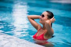 Tenned härlig asiatisk kvinna i orange bikini och sunlasses som sitter i simbassäng Trendig stående elegantt Royaltyfri Bild