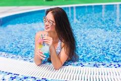 Tenned härlig kvinna i blå bikini och sunlasses som sitter i simbassäng med coctailen Trendig stående Arkivbilder
