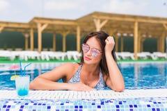 Tenned härlig kvinna i blå bikini och sunlasses som sitter i simbassäng med coctailen Trendig stående Arkivfoton