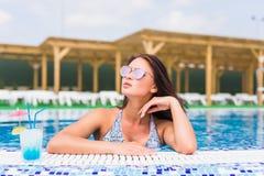 Tenned härlig kvinna i blå bikini och sunlasses som sitter i simbassäng med coctailen Trendig stående Royaltyfria Bilder