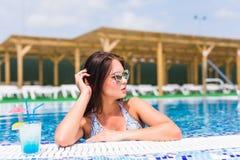 Tenned härlig kvinna i blå bikini och sunlasses som sitter i simbassäng med coctailen Trendig stående Royaltyfri Bild