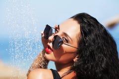 Tenned härlig kvinna i svart bikini och sunlasses som in sitter Fotografering för Bildbyråer