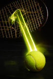 Tennis. Powerful tennis ball breaking through racket with strings broken leaving a forcefull yellow beam royalty free stock images