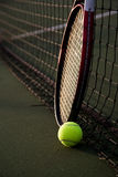 Tennis. A shot of a tennis racquet and a tennis ball leaning against the net on a tennis court Stock Photography