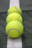 Tennis. Balls rest on the court line with the shadow of the net Stock Image