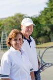 Tennis. Close up of a pair of senior male and female tennis players holding racquets Royalty Free Stock Photography