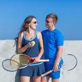 Tennis in abiti sportivi di tennis con la conversazione delle racchette di tennis Immagini Stock