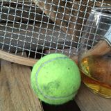 Tennis accessories by glass of whiskey Royalty Free Stock Photo