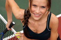Beautiful Tennis Player Female at Court Net. Fit and Attractive Female looks up at the camera from the net holding racket and ball stock photos
