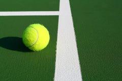 Tennis anyone. Yellow tennis ball on a green court Stock Image