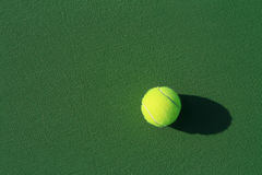Tennis anyone. Yellow tennis ball on a green court Royalty Free Stock Images