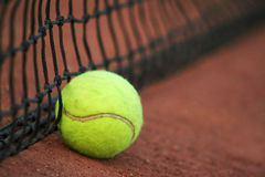 Tennis ball. On a red court with the tennis net stock photo
