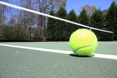Tennis Ball. A tennis ball on the court with the net in the background Stock Photos