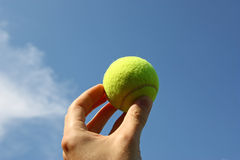 Tennis ball. On the blue sky background with hand Royalty Free Stock Photos