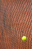 Tennis ball. The tennis ball has got stuck in a metal grid Stock Photo