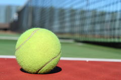 Tennis Ball. A Tennis ball sitting on a green and red court with the net in the background stock photos