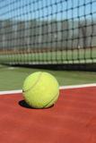 Tennis Ball. A Tennis ball sitting on a green and red court with the net in the background royalty free stock photo