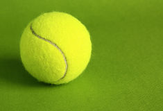 Tennis ball. On a green background Royalty Free Stock Image