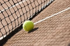 Tennis ball. Detail of yellow tennis ball on a clay court Royalty Free Stock Photos