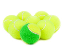 Tennis ball. A  green tennis ball in the front of yellow tennis balls on a white background Royalty Free Stock Image