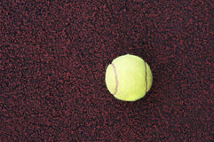 Tennis ball. A yellow tennis ball on the ground Royalty Free Stock Photos