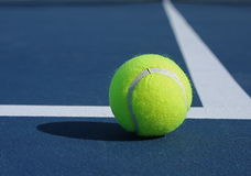 Tennis Ball at Baseline. Yellow tennis ball at the baseline of a blue court Stock Photography