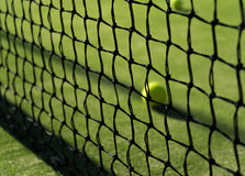 Tennis ball behind the net. In sunny day in May Stock Photos